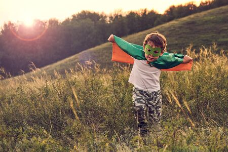 Photo pour little boy playing a superhero. Kid in an Superheros costume. happy child runs to meet the photographer. - image libre de droit