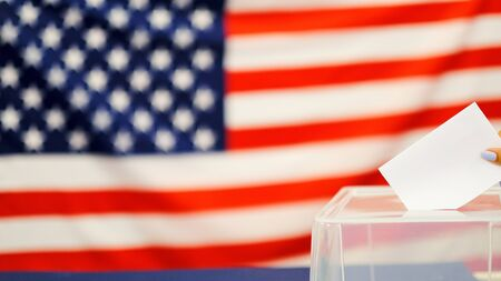 Photo pour woman putting a ballot in a ballot box on election day. Close up of hand with white votes paper on usa flag background - image libre de droit