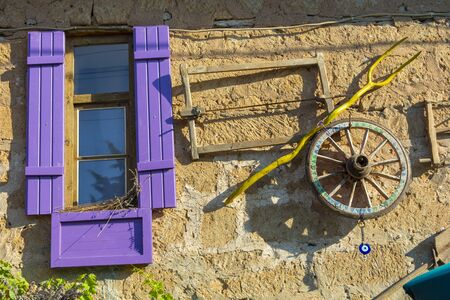 Photo pour mudbrick house with purple shutters. Hanging agricultural equipment on wall - image libre de droit