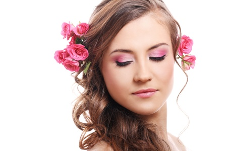 Beautiful woman with roses in hair over white background