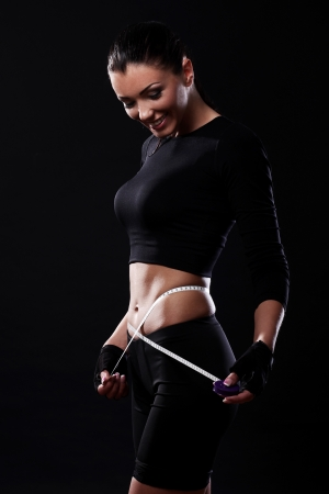 Photo for Happy fitness girl measuring her waistline over black background - Royalty Free Image