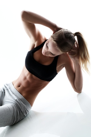 Foto de sporty and attractive woman do fitness exercise isolated on a white - Imagen libre de derechos