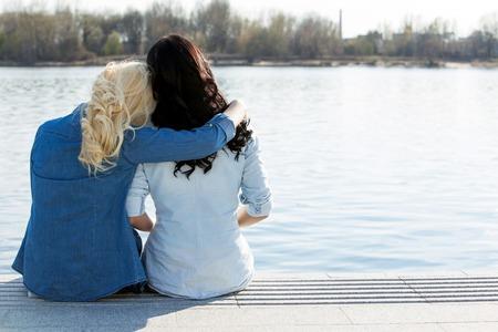 Photo pour Friendship  Best friends sitting by the river - image libre de droit
