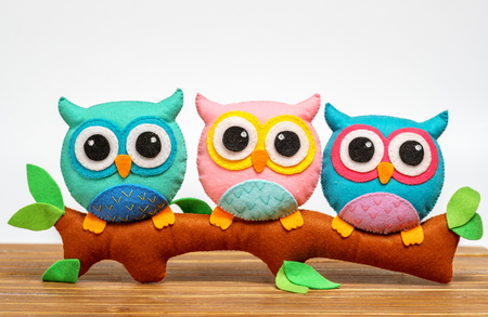 Photo for toy owls handmade on a branch. light background - Royalty Free Image