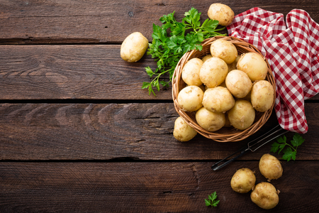Photo for Raw potato in basket on wooden table, top view - Royalty Free Image