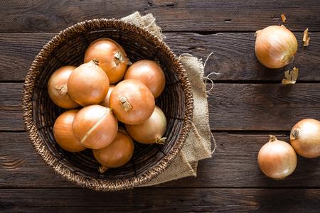 Foto de Fresh onion in basket on wooden table, top view - Imagen libre de derechos