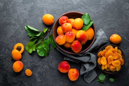 Photo for Fresh apricots with leaves and dried in bowl on table - Royalty Free Image