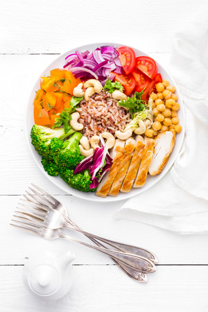 Photo pour Buddha bowl dish with chicken fillet, brown rice, pepper, tomato, broccoli, onion, chickpea, fresh lettuce salad, cashew and walnuts. Healthy balanced eating. Top view. White background - image libre de droit