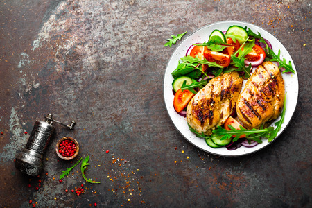 Foto de Grilled chicken breast. Fried chicken fillet and fresh vegetable salad of tomatoes, cucumbers and arugula leaves. Chicken meat with salad. Healthy food. Flat lay. Top view. Dark background - Imagen libre de derechos