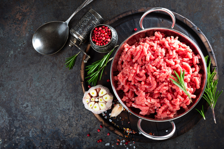 Foto de Cooking mince. Raw ground veal meat with ingredients for cooking on black kitchen table. Fresh minced meat, top view - Imagen libre de derechos