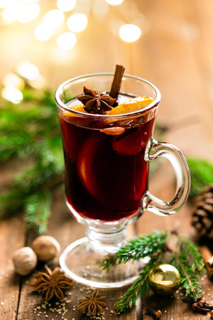 Photo pour Christmas mulled red wine with spices and oranges on a wooden rustic table. Traditional hot drink at Christmas - image libre de droit
