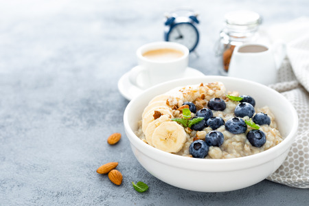 Photo for Oatmeal with fresh blueberry, banana, almond nuts and honey for breakfast - Royalty Free Image