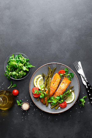 Photo for Grilled salmon fish steak, asparagus, tomato and corn salad on plate. Healthy dish for lunch. Top view - Royalty Free Image