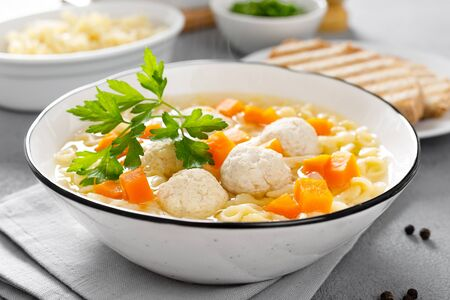 Photo for Hot chicken soup, broth with meatballs, carrot, pasta and fresh parsley - Royalty Free Image