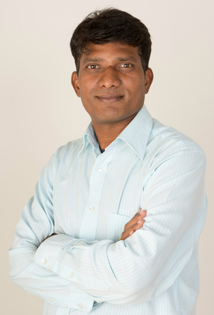 An Indian / South Asian business executive with folded arms looking to camera. On grey background.