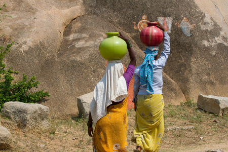 Photo for Two Indian women carry water on their heads in traditional pots - Royalty Free Image