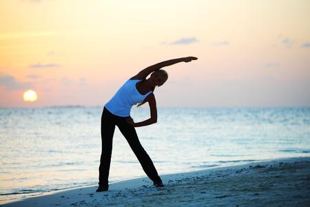 Photo for sunset yoga woman on sea coast - Royalty Free Image