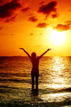 Photo for happy woman standing on a sunset in ocean waves - Royalty Free Image