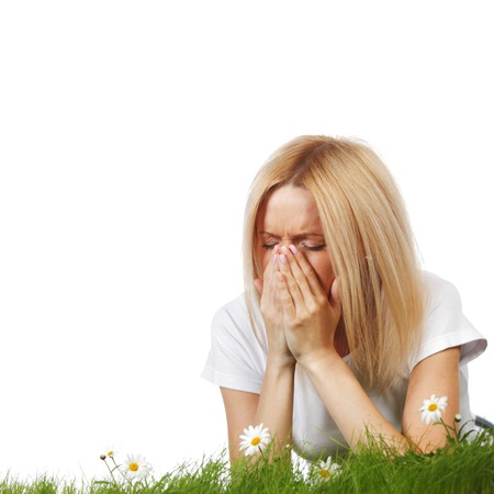 Foto de Pollen allergy, woman sneezing in a field of flowers - Imagen libre de derechos