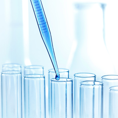 Foto de Laboratory pipette with drop of liquid over glass test tubes in a science research lab - Imagen libre de derechos