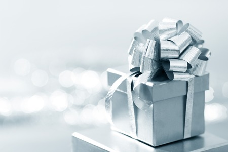 Photo for Holiday gift in silver box decorated with ribbon and bow - Royalty Free Image