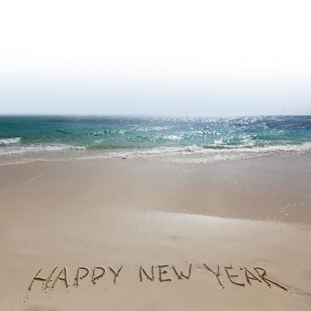 Photo pour Happy new year handwriting on tropical sea beach - image libre de droit
