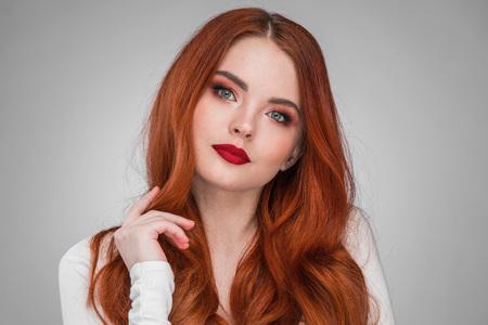 Foto de Beauty portrait of woman. Gorgeous sensual attractive pretty redhead sexy model girl, shiny wavy hair. - Imagen libre de derechos