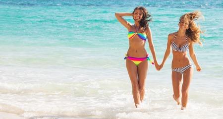 Photo pour Happy smiling female friends walking in sea waves - image libre de droit
