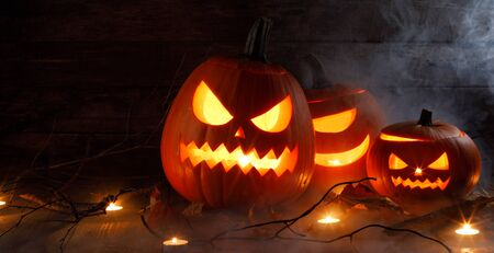 Photo pour Halloween pumpkin heads jack o lantern and candles in fog on wooden background - image libre de droit