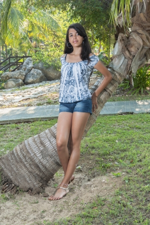 Hispanic girl leaning to a coconut tree
