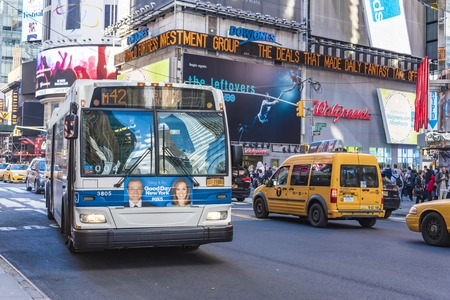 Public Transportation Bus in New York City Blue-white bus driving in a prominent street in New York City. A lot of traffic and advertisements in the background.