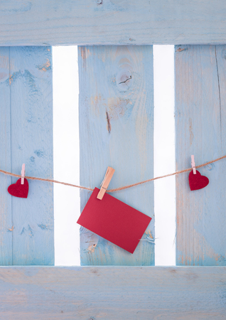 Photo for Unwritten red paper note surrounded by red hearts, tied to a linen string with wooden clips, on a blue fence. - Royalty Free Image