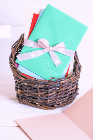 Photo for Unwritten message card and a wicker basket full of colorful envelopes, tied together with pink ribbon and bow, on a white wooden background. - Royalty Free Image
