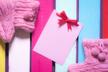 Photo for Unwritten pink paper note with red bow surrounded by handmade knitted pink bootees, on a multicolored wooden background. - Royalty Free Image