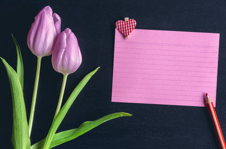 Photo for Greeting card idea with pink tulips a red notebook sheet with stripes, a wooden pencil and a wooden clip with a heart on it, on a black background. - Royalty Free Image