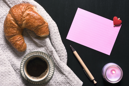 Photo for Cup of black coffee and a croissant, on a vintage kitchen towel, with a pink notebook sheet and a pen near, a lit pink candle, on a black table. - Royalty Free Image