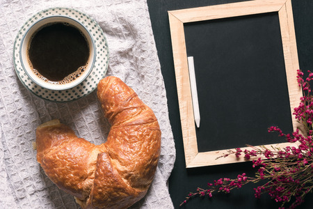 Photo for Breakfast table with a cup of coffee and a croissant on a vintage kitchen towel, near an empty chalkboard surrounded by flowers, on a black table. - Royalty Free Image