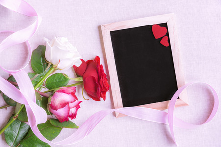 Photo for Lovely bouquet of multicolored roses, tied with a pink ribbon, near a blank chalkboard decorated with two red hearts, on a pink background. - Royalty Free Image
