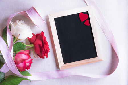 Photo for Valentine day theme image with beautiful roses tied with pink ribbon and a blank chalkboard decorated with two red hearts. - Royalty Free Image