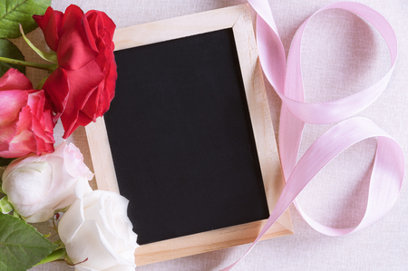 Photo for Unwritten chalkboard surrounded by beautiful colorful roses and a pink ribbon. Perfect frame for birthdays, mother day and valentine day. - Royalty Free Image