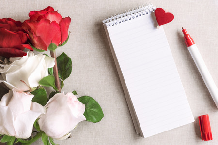 Photo for Open spiral notebook with stripes and a wooden clip with red heart pinned on it and a bouquet of white and red roses, on a vintage fabric background. - Royalty Free Image