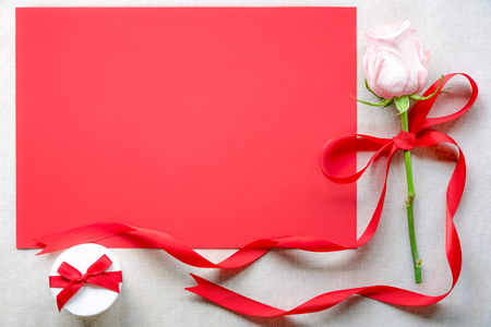 Photo for Anniversary frame design with a rose tied with red ribbon and bow, a gift box and a blank red paper sheet with space for text, on a vintage fabric. - Royalty Free Image