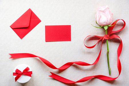 Photo for Birthday card with a cute gift box, a pink rose tied with red ribbon and bow, an envelope and a blank message card, on a vintage fabric background. - Royalty Free Image