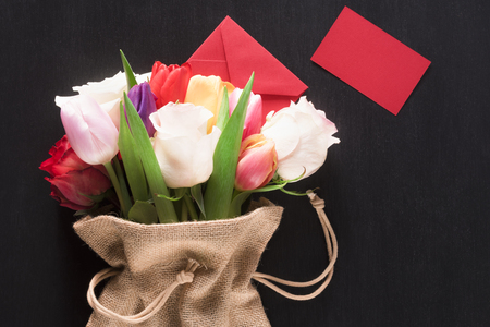 Photo for Greeting card with a bouquet of roses and tulips, wrapped in a hessian bag, a closed envelope and a red paper note, on a black wooden background. - Royalty Free Image