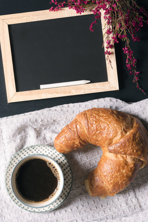 Photo for Breakfast arrangement with a cup of coffee, a croissant on a vintage kitchen towel and a chalkboard decorated with pink flowers, on a  black table. - Royalty Free Image