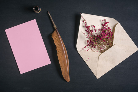 Photo for Vintage envelope full with pink flowers, an antique quill pen, an ink pot and a blank message card, on a black wooden background. - Royalty Free Image