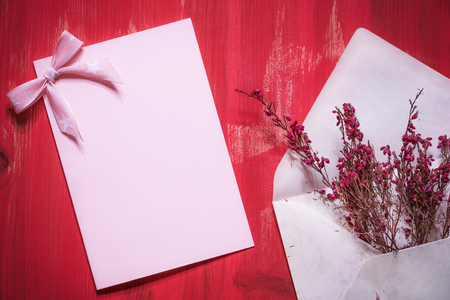 Photo for Greeting card idea with an open envelope full of beautiful red flowers near an empty pink paper note with a ribbon bow, on a red wooden background. - Royalty Free Image