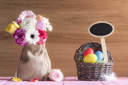 Photo for Bouquet of flowers in a jute sack and a wicker basket with painted eggs and a blank wooden banner, on a pink table, with a wooden wall. - Royalty Free Image