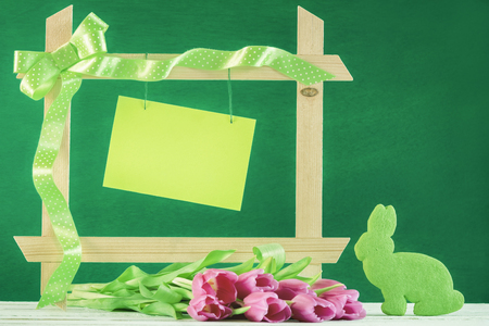 Photo for Easter greeting card with a wooden frame decorated with green ribbon, a blank message card and pink tulips and a bunny shaped green cookie. - Royalty Free Image