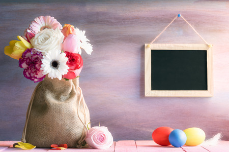 Photo for Easter banner with a bouquet of flowers in a jute sack, painted eggs and a blank blackboard hanging on a purple wooden background, on a sunny day. - Royalty Free Image
